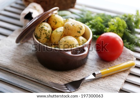 Young boiled potatoes in pan on wooden table - stock photo