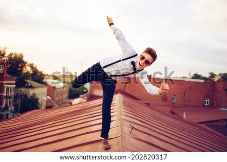 Young bold girl woman in hipster clothes, jumping on the roof, dressed like a boy man in a shirt, bow-tie, suspenders and pants trousers - stock photo