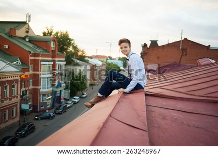 Young bold guy girl woman in hipster clothes, sit on edge of roof, dressed like a boy man in shirt, bow-tie, suspenders and pants trousers on background of city, road and jam - stock photo