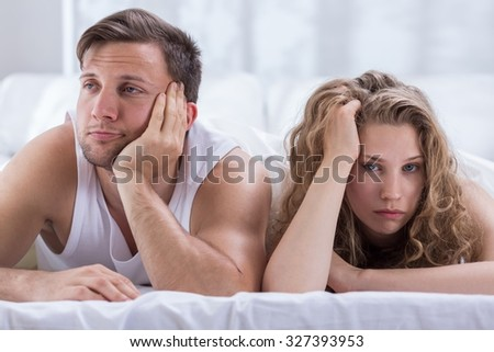 Young bored couple having problems in bedroom - stock photo