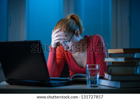 young  bored female college student studying poorly at late evening before exam, funny night procrastination concept - stock photo