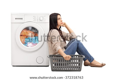 Young bored woman sitting by a washing machine and waiting for the laundry isolated on white background - stock photo