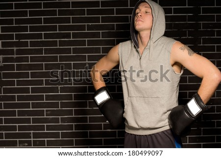 Young boxer doing breathing exercises before a fight standing with his gloved hands on his hips and head tilted back in the darkness with copyspace - stock photo