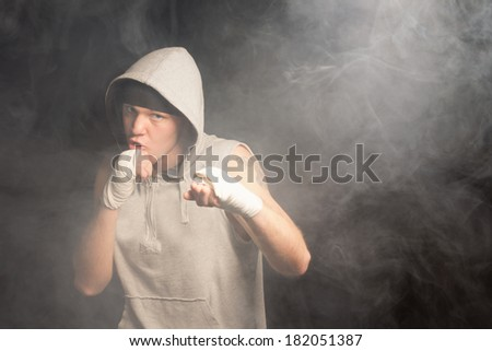 Young boxer fighting with bandaged fists in a smoky dark environment wearing a grey hooded top - stock photo