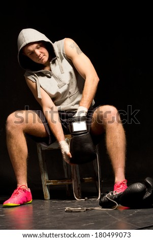 Young boxer getting ready for a training session sitting on a wooden stool fitting his gloves over his bandaged fists - stock photo