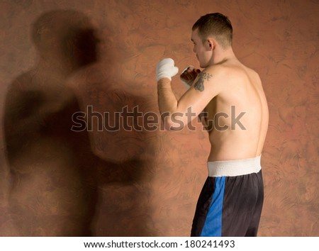 Young boxer in fitness training working out casting a shadow on a dark brown background with copyspace - stock photo