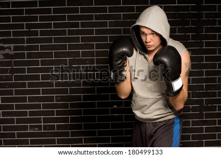 Young boxer training for a fight crouched forwards with his gloved fists raised during a practice round against a dark brick wall with copyspace - stock photo