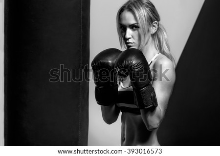 young boxer woman in boxing gloves with punching bag , on black and yellow background, black-and-white horizontal photo - stock photo