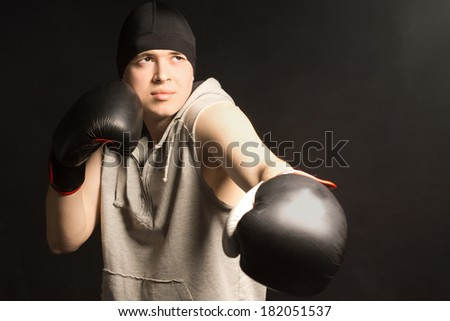 Young boxer working out in a training session frowning as he does not quite manage to pull off the punch correctly on a dark background - stock photo