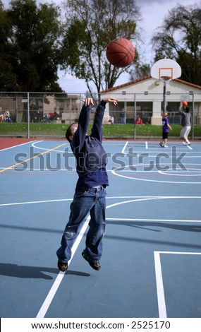 Young boy airborne while shooting a basketball - stock photo