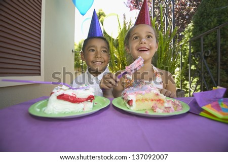 Young boy and girl at birthday party - stock photo