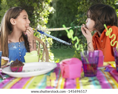 Young boy and girl blowing party puffers at each other in outdoor birthday party - stock photo