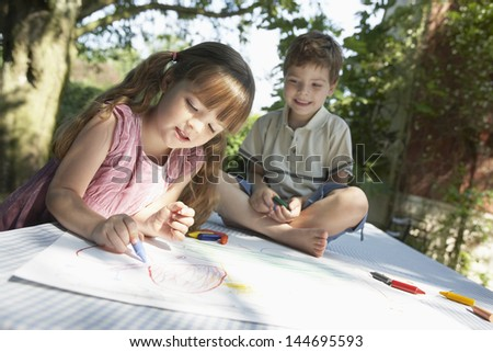 Young boy and girl drawing on table in back garden - stock photo