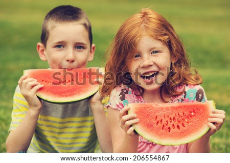 Young boy and girl eating watermelon, toned image - stock photo