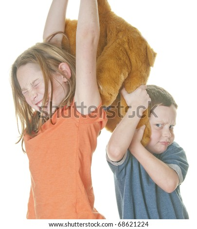 young boy and girl fighting over bear - stock photo