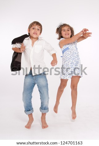 Young boy and girl happily jumping - stock photo
