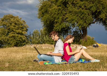 Young boy and girl in park with laptop and book - stock photo