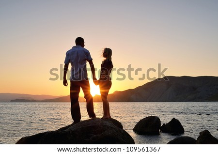 Young boy and girl look at each other, hand in hand on the beach at sunset - stock photo