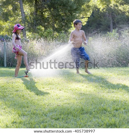 Young boy and girl playing with water in the garden - stock photo