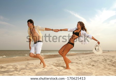 young boy and girl running on beach - stock photo