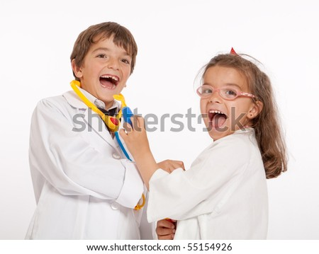 Young boy and girl with medical uniforms playing with toy doctor instruments - stock photo
