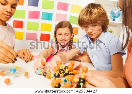 Young boy and girls assembling molecule model - stock photo