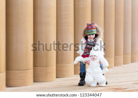 Young boy and his baby sister on a walk next to a modern building entrance with pillars - stock photo