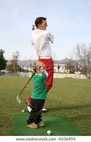 Young boy and his father practicing on the driving range. Focus set on child. - stock photo