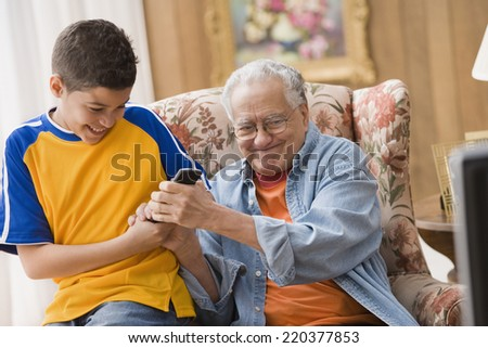 Young boy and his grandfather fighting over the remote control - stock photo