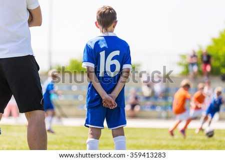 Young boy and soccer coach watching football match. Youth reserve player ready to play - stock photo