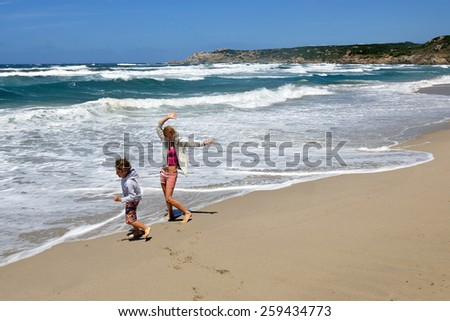 Young boy and woman playing, running, jumping and having fun in the surf on the beach - stock photo