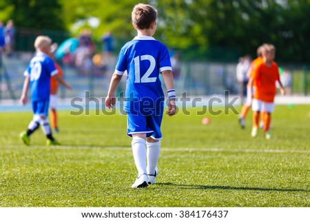Young boy as a soccer football player at a sports stadium. Youth soccer football match at school tournament. - stock photo