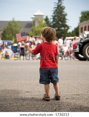 Young boy at a parade with an American Flag - stock photo