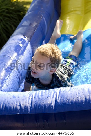 Young boy at bottom of water side laughing - stock photo