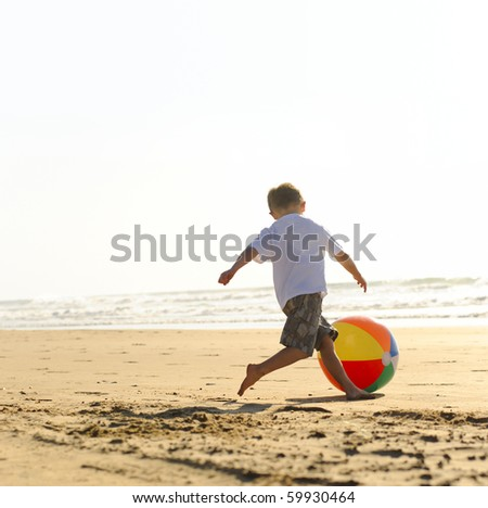 Young boy at the beach plays with a big beachball - stock photo