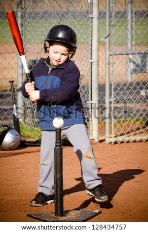 Young boy batting at T-ball practice - stock photo