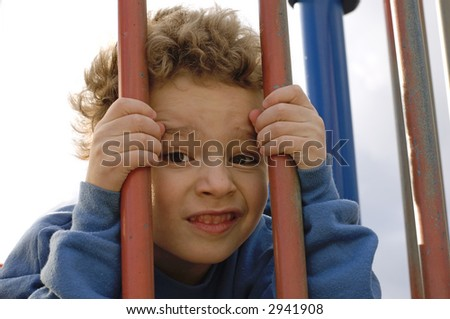 Young boy behind bars on playground equipment - stock photo