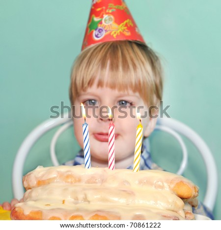 Young boy blowing birthday candles - stock photo