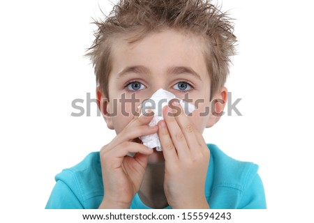 Young boy blowing his nose - stock photo