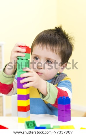 Young boy builds a tower with connecting blocks - stock photo
