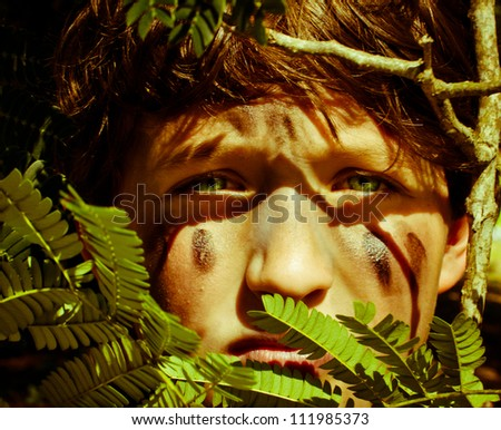 Young boy camouflaged behind tree leaves. - stock photo
