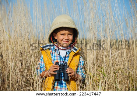 Young boy child playing pretend explorer adventure safari game outdoors with binoculars and bush hat - stock photo