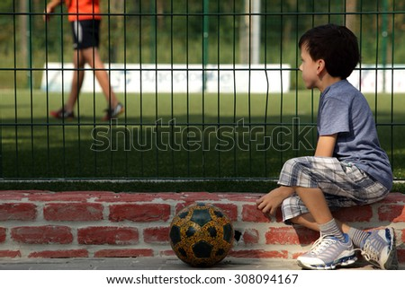 Young boy child watching organized youth soccer or football game for grid - stock photo