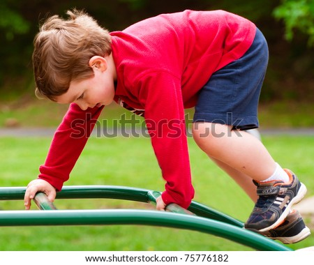 Young boy climbing on playground during spring. - stock photo