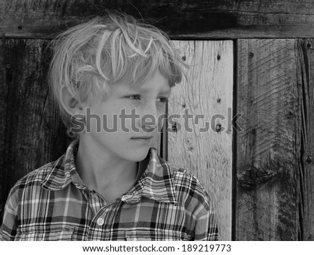 Young boy contemplating with a rustic wooden background. - stock photo