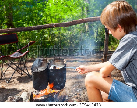 Young boy cooking camp food in cauldron on open fire - stock photo