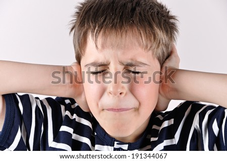 Young boy covering his ears with hands and closed mouth and eyes because of loud noise - stock photo
