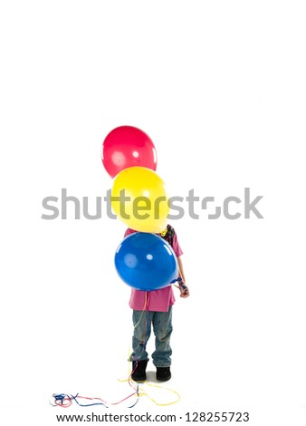 Young boy covers face with party balloons. - stock photo