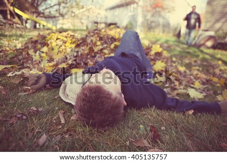 Young boy daydreaming in a pile of fall leaves, slacking on the job, shallow focus - stock photo