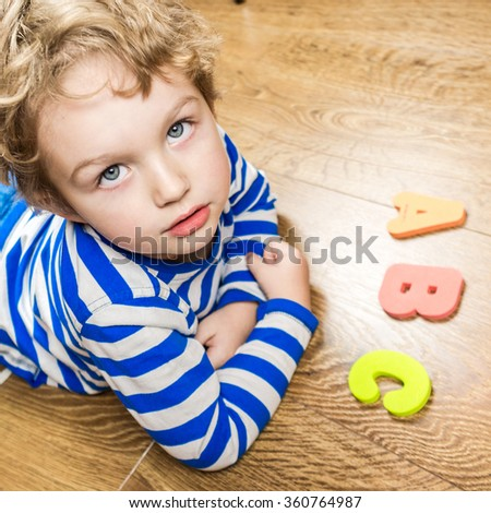 young boy demonstrating his collection of capital letters with thoroughly face while laying on brown wooden floor - stock photo